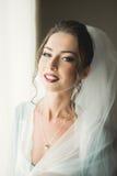 Piękna młoda panna młoda z makeup i fryzura w sypialni, nowożeńcy kobiety definitywny przygotowanie dla poślubiać szczęśliwa dzie Fotografia Stock