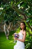 Piękna młoda panna młoda pozuje w ślubnej sukni z tropikalnego drzewnego mienia ślubnym bukietem obrazy stock