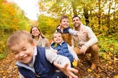 Piękna młoda rodzina na spacerze w jesień lesie Zdjęcie Royalty Free