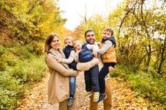 Piękna młoda rodzina na spacerze w jesień lesie Zdjęcia Stock