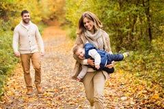 Piękna młoda rodzina na spacerze w jesień lesie Fotografia Royalty Free