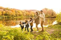 Piękna młoda rodzina na spacerze w jesień lesie fotografia stock