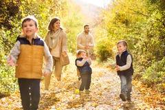 Piękna młoda rodzina na spacerze w jesień lesie zdjęcie stock
