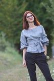 Piękna młoda rudzielec kobieta pozuje w natury zieleni polu Zdjęcia Royalty Free