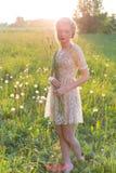 Piękna młoda słodka dziewczyna w białej sukni z włosy na kierowniczych pochylonych spacerach w polu przy zmierzchem Obraz Royalty Free