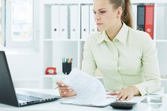 Piękna młoda sekretarka patrzeje laptopu obsiadanie przy biurem robi notatkom fotografia stock
