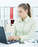 Piękna młoda sekretarka pracuje na laptopu obsiadaniu przy biurem Obraz Stock