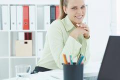 Piękna młoda sekretarka trzyma jej głowę siedzi przy biurem w ona ręki Obraz Royalty Free