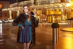 Piękna młoda seksowna blondynka jest ubranym wieczór makeup w eleganckiej dopasowanie sukni futerkowego żakieta spaceru nocy modn Fotografia Stock