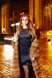 Piękna młoda seksowna blondynka jest ubranym wieczór makeup w eleganckiej dopasowanie sukni futerkowego żakieta spaceru nocy modn Zdjęcie Stock