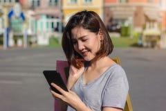 Piękna młoda shopaholic Azjatycka kobieta używa smartphone dla opowiadać podczas gdy chodzi kupować kosmetyki, odziewa etc zdjęcie stock