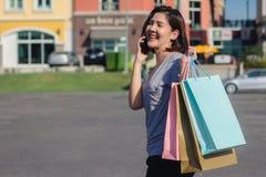 Piękna młoda shopaholic Azjatycka kobieta używa smartphone dla opowiadać podczas gdy chodzi kupować kosmetyki, odziewa etc fotografia royalty free