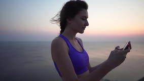 Piękna młoda sportowa dziewczyna w purpurowym wierzchołku bierze selfie przeciw tłu ocean przy zmierzchem lub wschód słońca A zbiory wideo