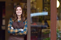 Piękna młoda sprzedawczyni patrzeje kamerę i opiera przeciw drzwiowej ramie organicznie sklep zdjęcie stock