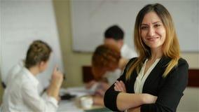 Piękna młoda uśmiechający się fachowa kobieta w biurze, składać ręki i ufny wyrażenie jako inni pracownicy, trzymamy a zbiory wideo