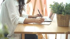 Piękna młoda uśmiechnięta Azjatycka kobieta pracuje na laptopie w biurowej pracy przestrzeni podczas gdy w domu zbiory