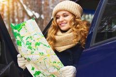 Piękna młoda uśmiechnięta dziewczyna siedzi w samochodu i mienia mapie w jej rękach, jest ubranym niebieską marynarkę Podróży dzi Zdjęcia Royalty Free