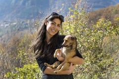 Piękna młoda uśmiechnięta kobieta ściska psa Fotografia Royalty Free
