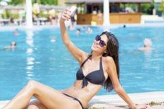 Piękna młoda uśmiechnięta kobieta ma zabawę robi selfie Zdjęcia Royalty Free