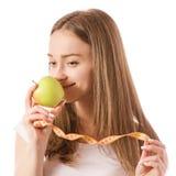 Piękna młoda uśmiechnięta kobieta trzyma pomiarowego centymetra w rękach i jabłka Fotografia Stock
