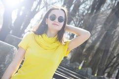 Piękna młoda uśmiechnięta kobieta w kolor żółty sukni w parku w pogodnej pogodzie fotografia stock