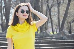 Piękna młoda uśmiechnięta kobieta w kolor żółty sukni w parku w pogodnej pogodzie zdjęcie royalty free