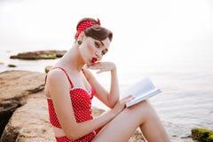 Piękna młoda urocza szpilka w górę dziewczyny czytelniczej książki podczas gdy siedzący Zdjęcie Royalty Free