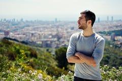 Piękna młoda wycieczkowicz pozycja na halnym wzgórzu i patrzeć oddalonym, dużym miasta tłem, Fotografia Royalty Free