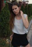 Piękna młodej dziewczyny pozycja z deskorolka w ręce Obrazy Royalty Free