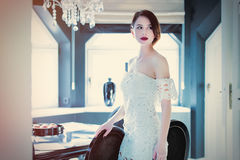 Piękna młodej kobiety pozycja blisko stołu w lekkim luxur Obrazy Stock