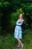 Piękna młodej kobiety pozycja z uśmiechem Portret piękna dziewczyna w biel sukni wśród drzew w lasowej dziewczynie Zdjęcie Stock
