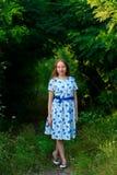 Piękna młodej kobiety pozycja z uśmiechem Portret piękna dziewczyna w biel sukni wśród drzew w lasowej dziewczynie Obraz Stock