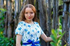 Piękna młodej kobiety pozycja z uśmiechem Portret piękna dziewczyna w biel sukni wśród drzew w lasowej dziewczynie Zdjęcie Royalty Free
