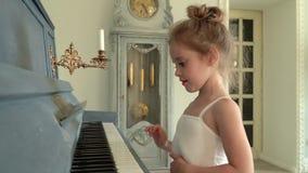 Piękna mała balerina w biel spódniczce baletnicy bawić się syntetyka Dziewczyna dotyków klucze na syntetyku zbiory