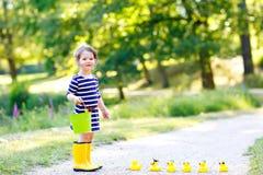 Piękna mała berbeć dziewczyna bawić się w parku Uroczy dziecko jest ubranym mod przypadkowych ubrania i żółtych gumowych buty Obrazy Royalty Free