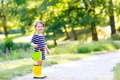 Piękna mała berbeć dziewczyna bawić się w parku Uroczy dziecko jest ubranym mod przypadkowych ubrania i żółtych gumowych buty Obraz Stock