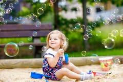 Piękna mała blondynka berbecia dziewczyna ma zabawę z dmuchać mydlanego bąbla dmuchawę Śliczny uroczy dziecka dziecko bawić się d obraz stock