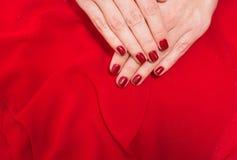 Piękna mała czerwona kobieta dotyka na czerwonej tkaniny teksturze Obrazy Stock