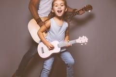 Piękna mała dziewczynka bawić się gitarę z jej ojcem zdjęcie royalty free