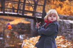 Piękna mała dziewczynka bawić się połów z gałąź i ryba zabawką Zdjęcia Royalty Free