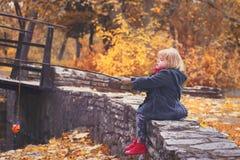 Piękna mała dziewczynka bawić się połów z gałąź i ryba zabawką w parku na zimnym jesień dniu, Obraz Stock