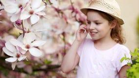 Piękna mała dziewczynka całuje Magnoliowego kwiatu w ogródzie zdjęcie wideo