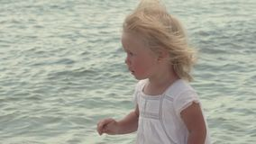Piękna mała dziewczynka chodzi wzdłuż seashore Mała dziewczynka w białej sukni na brzegowym zwolnionym tempie zdjęcie wideo