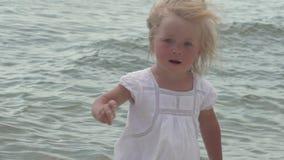 Piękna mała dziewczynka chodzi wzdłuż seashore Mała dziewczynka w białej sukni na brzegowym zwolnionym tempie zbiory