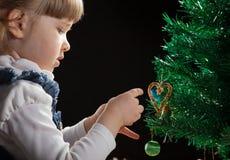 Piękna mała dziewczynka dekoruje choinki Zdjęcia Royalty Free
