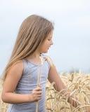 Piękna mała dziewczynka drzeje pszenicznych ucho w polu przy letnim dniem Pojęcie czystość, przyrost, szczęście Obrazy Royalty Free