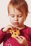 Piękna mała dziewczynka je Czekoladowego układu scalonego ciastko Fotografia Royalty Free