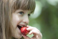 Piękna mała dziewczynka je soczystej czerwonej truskawki Fotografia Royalty Free