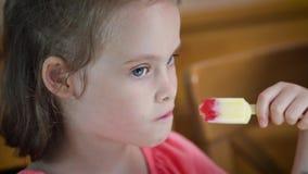 Piękna mała dziewczynka je wyśmienicie kolorowego lody zbiory
