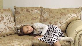 Piękna mała dziewczynka kłama puszek na kanapie przed iść spać zdjęcie wideo
